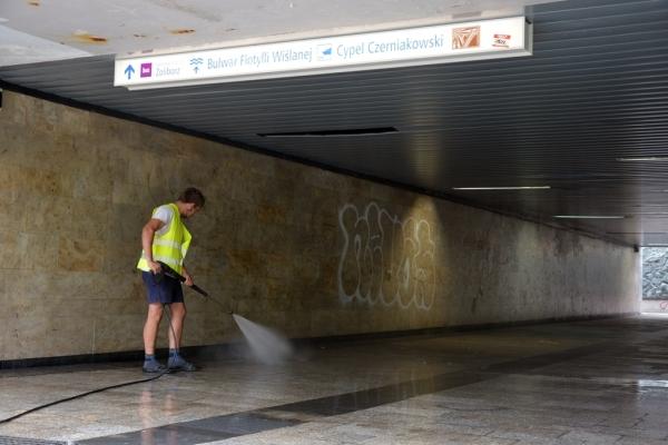 Pracownik firmy porządkowej myje myjką ciśnieniową chodnik w przejściu podziemnym