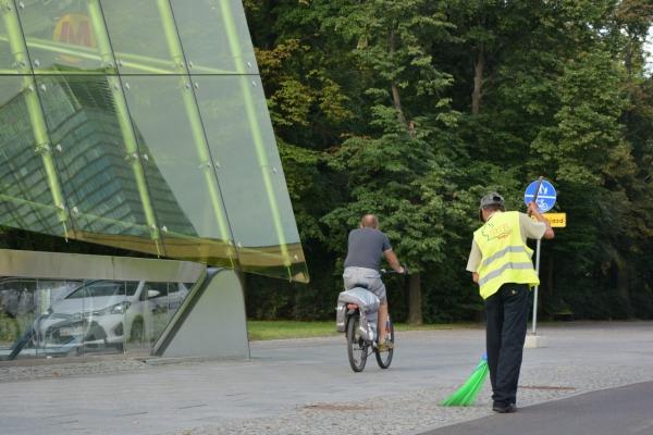 Pracownik firmy porządkowej zamiata chodnik przy wejściu do stacji metra Świętokrzyska