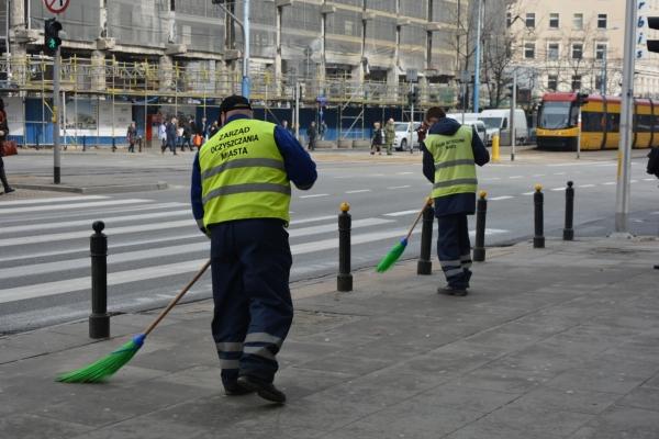 Pracownicy ZOM zamiatają chodnik przy przejściu dla pieszych