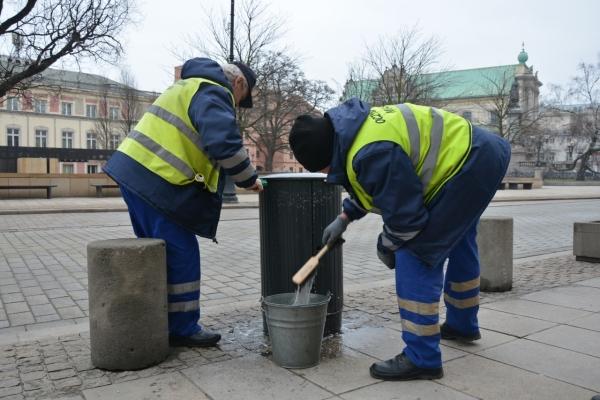 Pracownicy ZOM czyszczą żeliwny kosz na śmieci