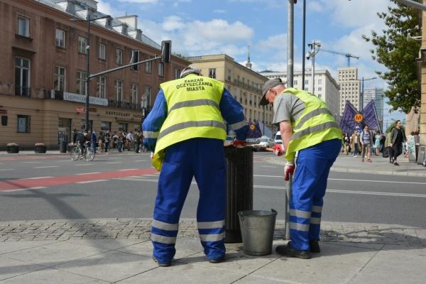 Pracownicy ZOM czyszczą żeliwny kosz na śmieci, kosz stoi przy skrzyżowaniu