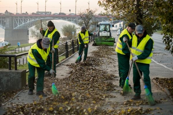 Pracownicy firmy porządkowej zamiatają chodnik z liści, za nimi jedzie sprzątający ciągnik. W tle most Poniatowskiego.