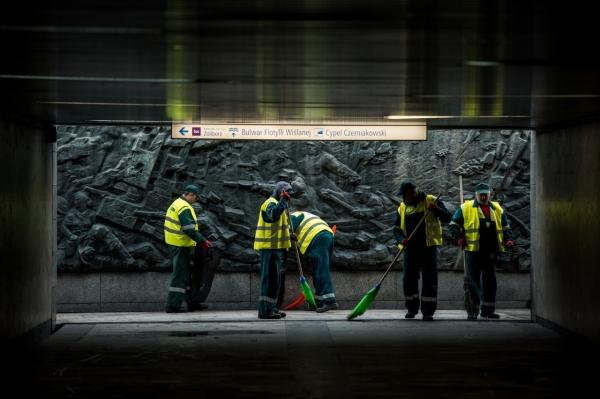 Grupa pracowników firmy porządkowej zamiata przejście podziemne. Pod sufitem znak informujący o kierunkach wyjść.