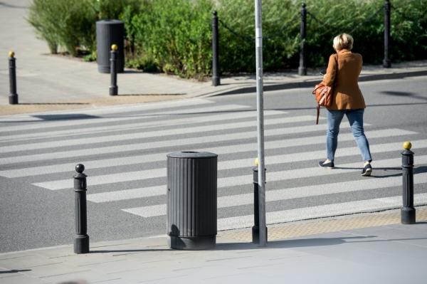Dwa żeliwne kosze na śmieci stojące przy przejściu dla pieszych, na chodnikach po dwóch stronach ulicy