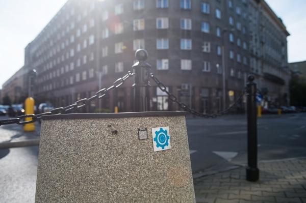 Betonowy kosz na śmieci oznaczony niebieskim trybikiem - znakiem budżetu obywatelskiego