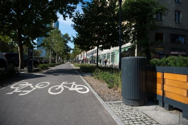 Żeliwny kosz na śmieci stojacy na chodniku, obok ścieżka rowerowa