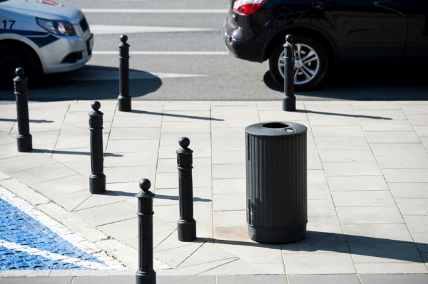 Żeliwny kosz na śmieci stoi na chodniku