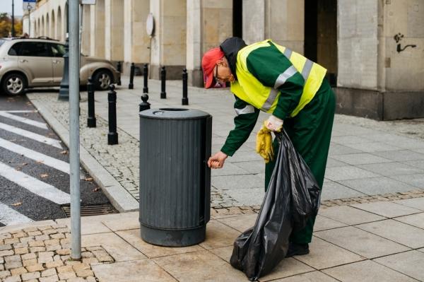 Pracownik firmy porządkowej otwiera żeliwny kosz na śmieci, w ręku trzyma worek na odpady