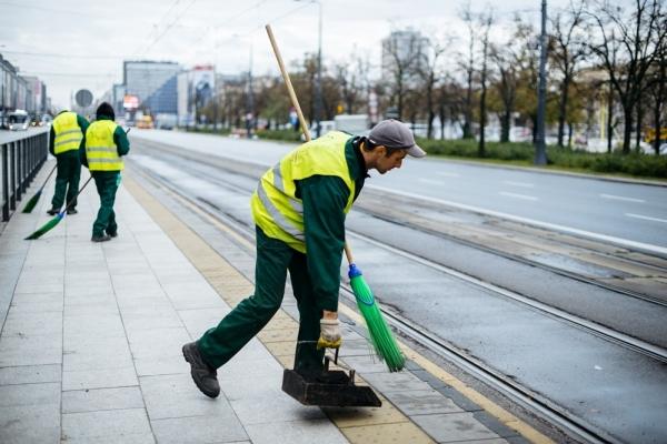 Ekipa porządkowa sprząta przystanek tramwajowy w centrum Warszawy