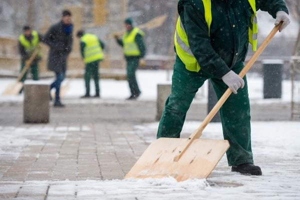 Pracownik zgarnia szuflą śnieg z chodnika