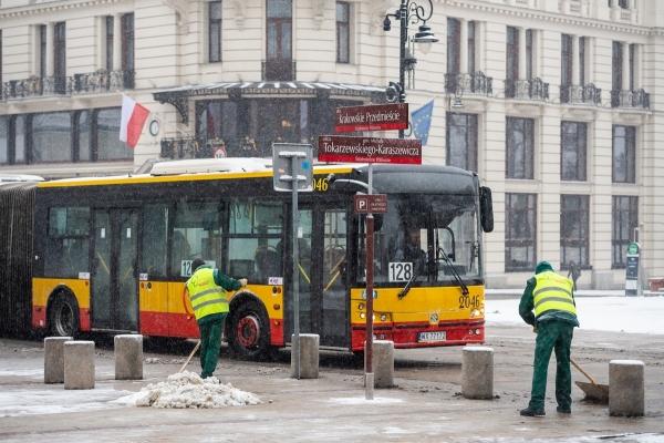 Pracownicy firmy porządkowej zgarniają śnieg z chodnika ul. Krakowskie Przedmieście, w tle przejeżdża autobus