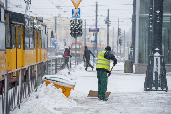 Pracownik firmy porządkowej zgarnia z chodnika przy wejściu do stacji metra Ratusz śnieg szuflą, obok przejeżdża tramwaj
