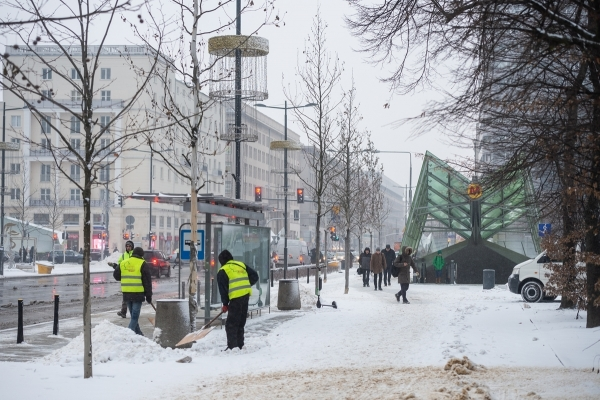 Pracownicy firmy porządkowej odśnieżają przystanek autobusowy, w tle wejście do stacji metra Świętokrzyska