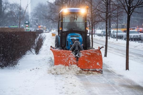Ciągnik z pługiem zgadnia śnieg z chodnika