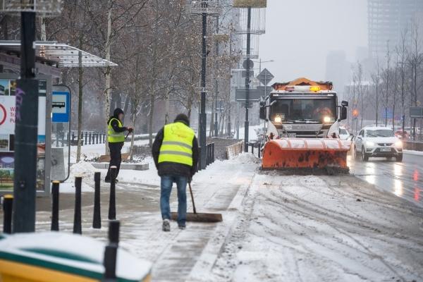 Ekpia sprzątająca odśnieża przystanek autobusowy, po ulicy jedzie pług zgarniający śnieg